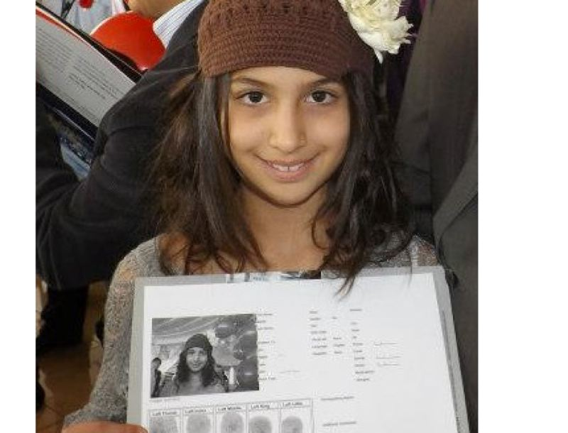 COURTESY PHOTO - A child poses proudly with Operation Kidsafe documents including fingerprints and a biography.