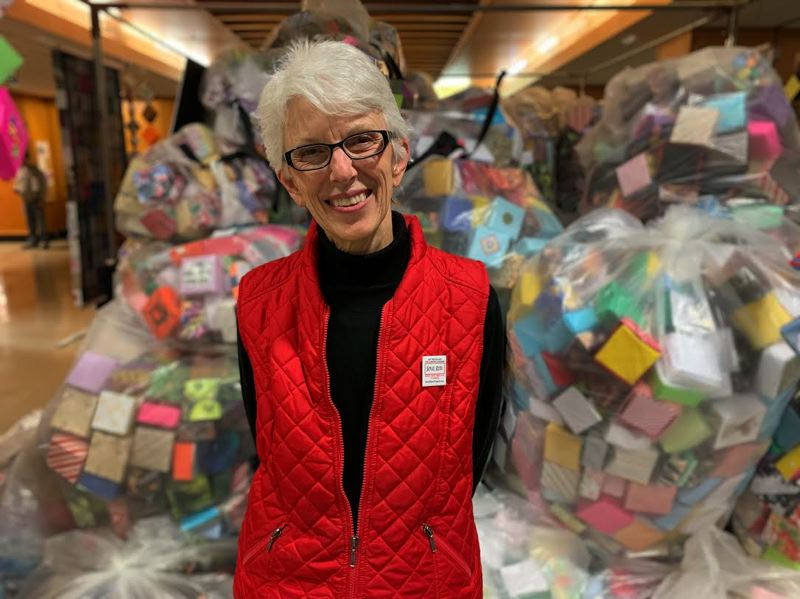 SUBMITTED PHOTO - Portland artist Leslie Lee, founder of The Soul Box Project, stands in front of bags of boxes created by volunteers.