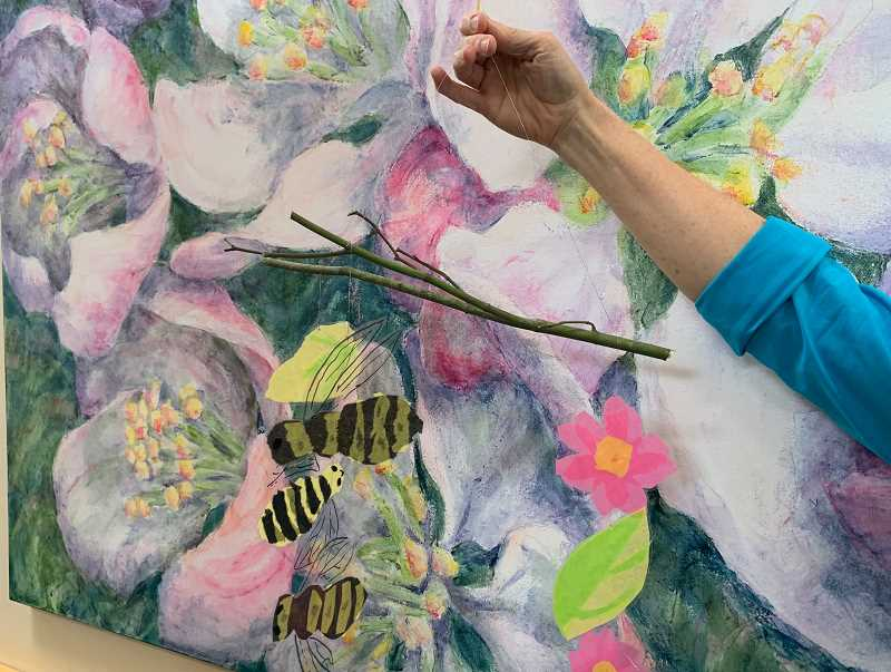 PMG PHOTO: JANAE EASLON - Artist Susan Curington holds up a flower and bee mobile she made as a demonstration in preparation for teaching fourth and fifth grade West Union Elementary School students.