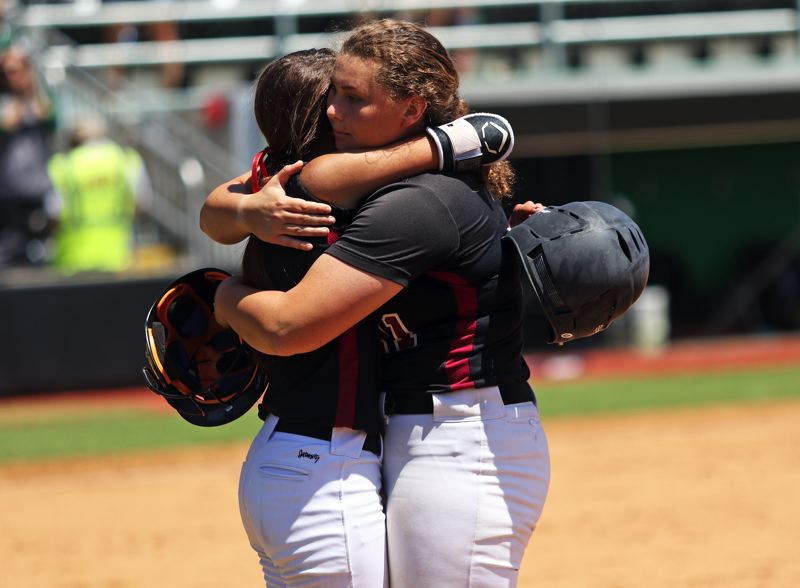 PMG PHOTO: DAN BROOD - Tualatin High School junior Tia Ridings (left) hugs senior Emily Johansen following the final out of the Timberwolves' 5-4 loss to Sheldon in Saturday's Class 6A state championship game.
