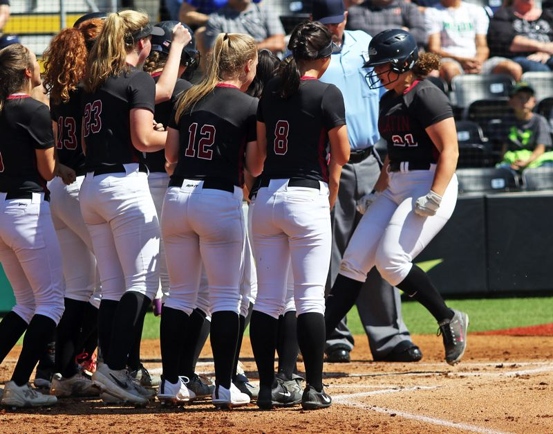 PMG PHOTO: DAN BROOD - Tualatin High School senior Emily Johansen (right) is greeted at home plate by her Timberwolf teammates following her first-inning, two-run home run in Saturday's Class 6A state championship game.