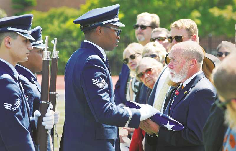 GRAPHIC PHOTO: GARY ALLEN - An honor guard from McChord Air Force Base in Washington presents Ken Austin III with an American flag during a celebration of life for Ken Austin Jr. Friday at Stoffer Field on the campus of George Fox University.