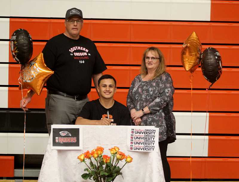 STEELE HAUGEN - Lorenzo Vasquez signs his letter of intent to wrestle at Southern Oregon University, in Ashland, with Culver wrestling coach J.D. Alley (left) and mother, Shantel Vasquez (right), at his side.