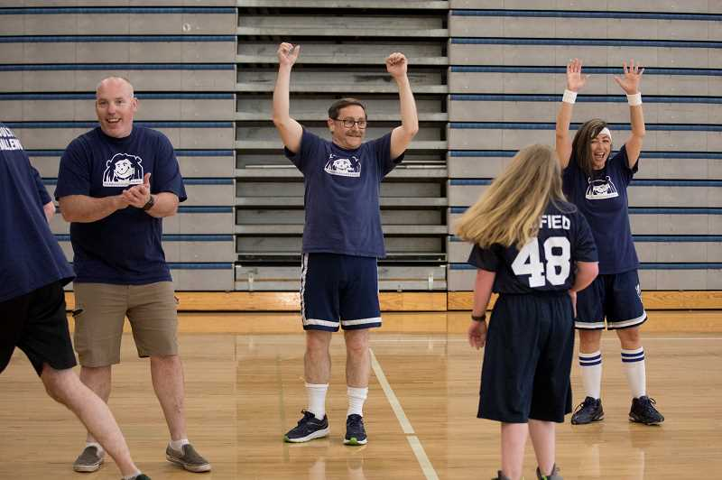 PMG PHOTO: JAIME VALDEZ - Wilsonville High School science teachers Jason Milham and Jim O'Connell, along with Athletic Secretary BJ Cerny, celebrate after a player from the Unified basketball team scores during Doernbecher Days at the high school.