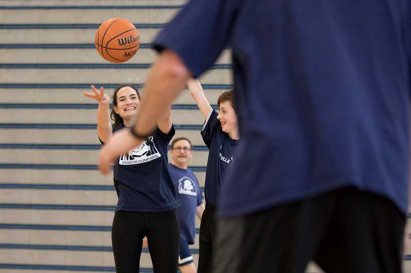 PMG PHOTO: JAIME VALDEZ - Annie Kubitschek, a science teacher at Wilsonville High School, attempts to pass to a fellow staff member while being guarded by Ben Schauer, a member of the Unified basketball team.