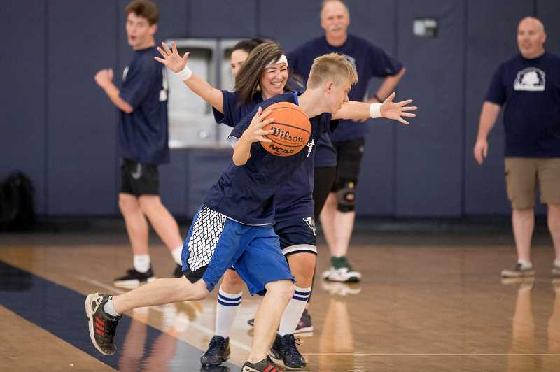 PMG PHOTO: JAIME VALDEZ - Wilsonville High School's Athletic Secretary BJ Cerny defends Michael Hasler, a player with the Unified basketball team during Doernbecher Days at the High School.