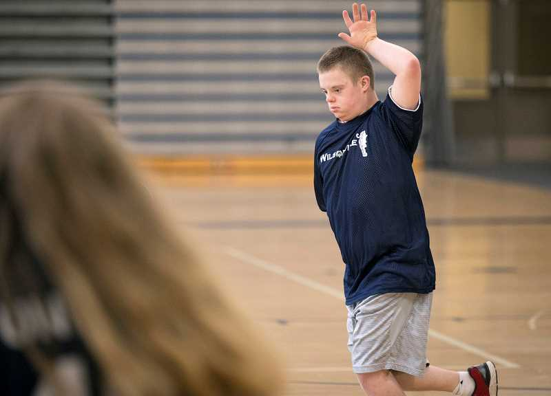PMG PHOTO: JAIME VALDEZ - Michael Hasler, a player with the Unified basketball team, celebrates after making a basket against the teachers at Wilsonville High School during Doernbecher Days.