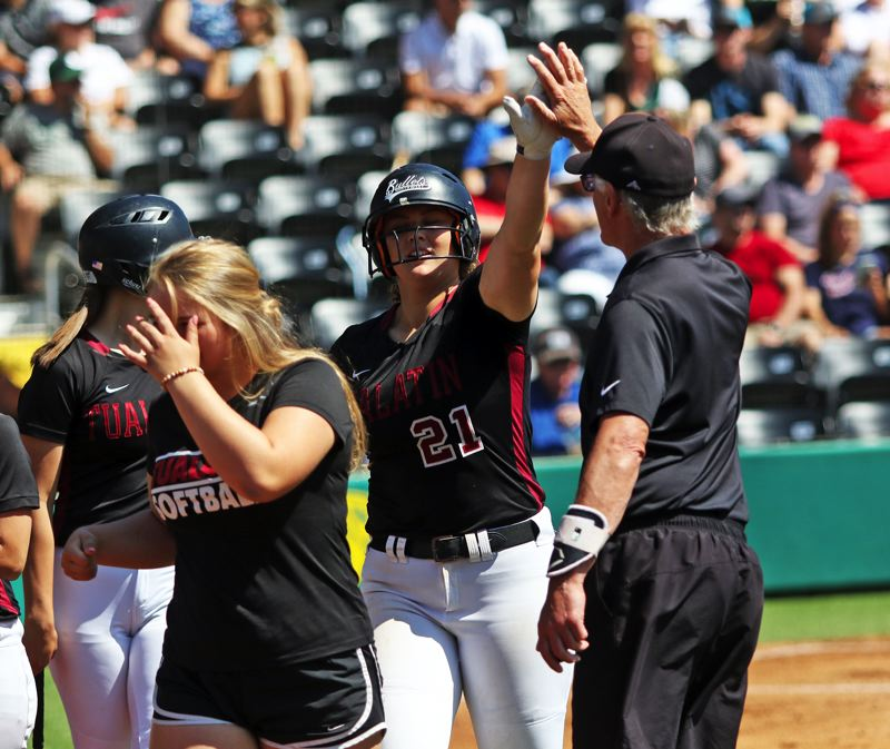 PMG PHOTO: DAN BROOD - Tualatin High School senior Emily Johansen (21) gets a high-five from assistant coach Bill Wilson after hitting a two-run, first-inning home run in Saturday's Class 6A state championship game.