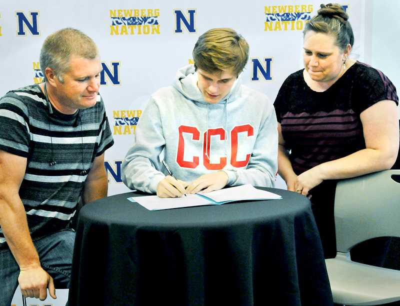 GRAPHIC PHOTO: RYAN CLARKE - With his family looking on, Newberg wrestler Joey Moody signed with Clackamas Community College on May 22.
