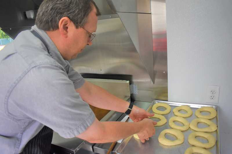 PMG PHOTO: EMILY LINDSTRAND - James Beachy puts doughnuts into the fryer.