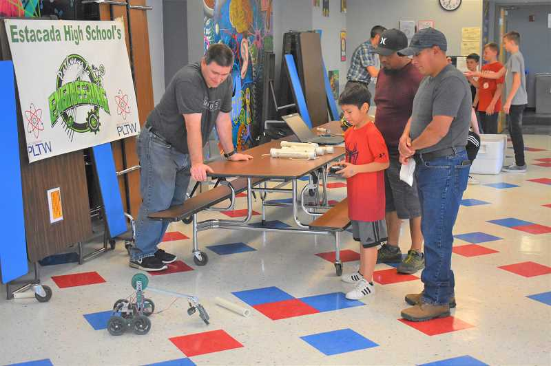 PMG PHOTO: EMILY LINDSTRAND - Families engage with robots during an Estacada Middle School event.