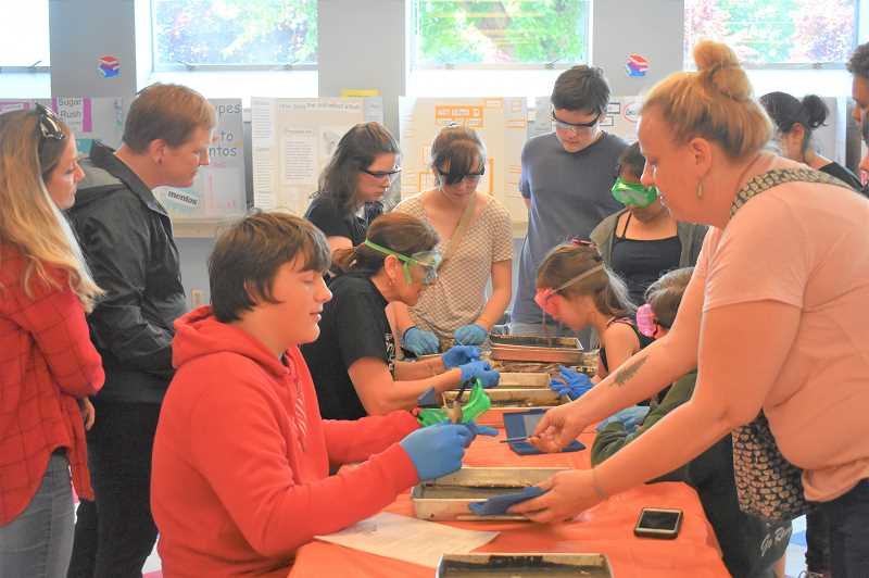 PMG PHOTO: EMILY LINDSTRAND - Attendees gather around as students prepare to dissect frogs.