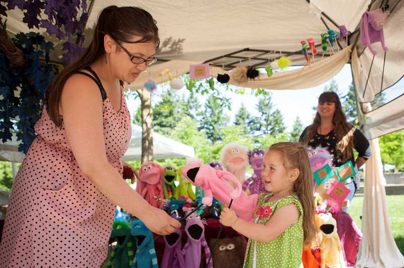 PMG PHOTO: JAIME VALDEZ - Marissa Galati watches her 3-year-old daughter, Lilly, play with a puppet as Nicole Ponce, owner of Ponster Puppets, watches at the Wilsonville Festival of the Arts.