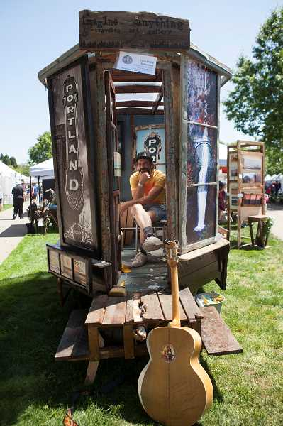 PMG PHOTO: JAIME VALDEZ - Photographer Lone Wolf Ballentine, owner of Imagine Anything from Sandy, stays cool inside his display at the Wilsonville Festival of the Arts.