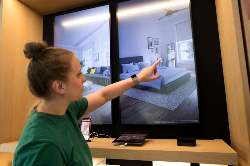 PMG: JAIME VALDEZ - New Avenues along the back wall allow limited hands-on experience with home control, gaming and audio equipment. Here a staffer shows how to set a bedroom to Party Time mode using an IOS device.