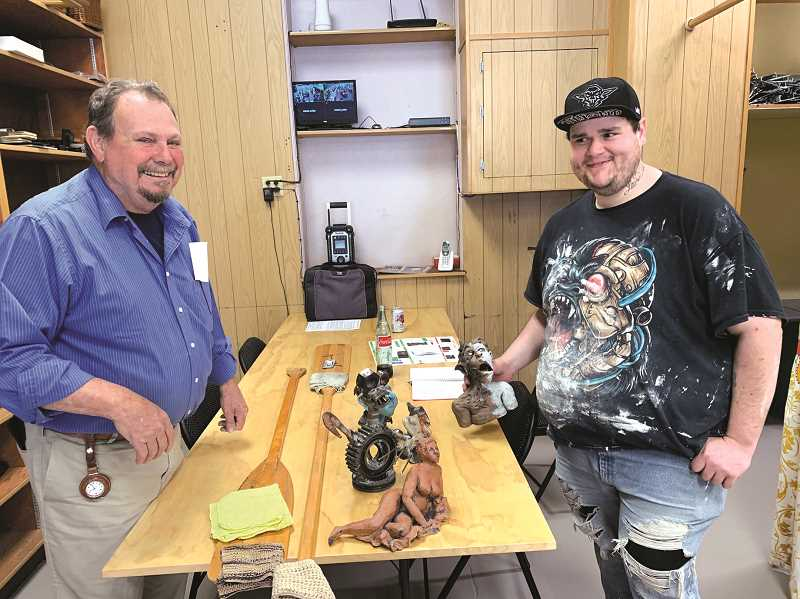 PMG PHOTO: CAROL ROSEN - Steve Mysinger (left) and Mark Hise display some of Mysinger's designs, some of which appear to be relatives of gargoyles. In all, there are 12 artists' works that are on display at the new Molalla gallery.