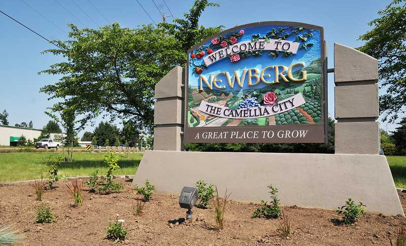 GRAPHIC PHOTO: GARY ALLEN - The southern entrance to Newberg on Highway 219 is now adorned with a renovated sign in keeping with the designation of Newberg as 'The Camellia City.'