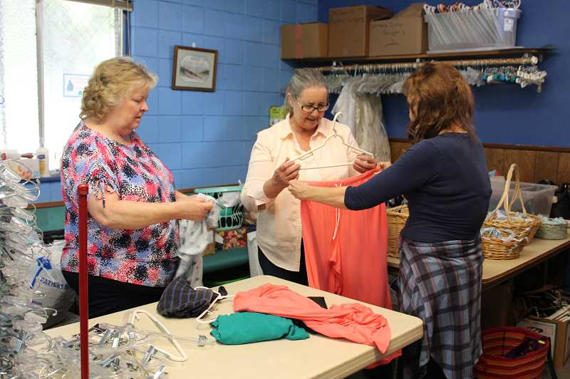 HOLLY SCHOLZ/CENTRAL OREGONIAN - Women of the Prineville Church of Christ sort clothing for their Clothing Room Ministry. Pictured left to right, Lynnetta Freie, Kathy Riley and Dianne Scalley.