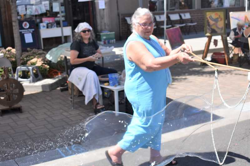 PMG PHOTO: EMILY LINDSTRAND - Estacada artist Annette Reisbick plays with bubbles during last year's Summer Celebration.