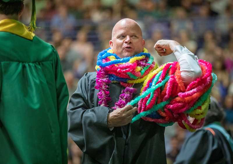 PMG PHOTO: JONATHAN HOUSE  - West Linn High Principal Greg Neuman finds a way to put on another Hawaiian lei during commencement.