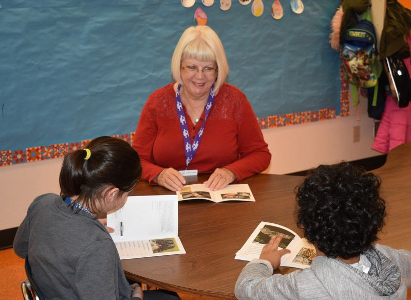 PMG PHOTO: TERESA CARSON  - Peggy Armstrong, a volunteer tutor with AARP Experience Corps, reads with two students at Greshams Hall Elementary School.