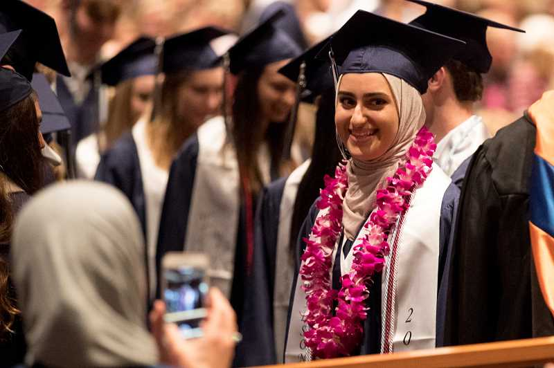 PMG PHOTO: JAIME VALDEZ - Senior Dana Zaidan has her picture taken by her mom, Eman Badwan, during Wilsonville High School's commencement ceremony at Rolling Hills Community Church.