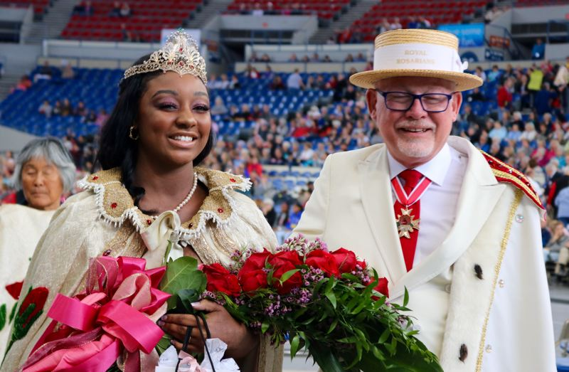 PMG PHOTO: ZANE SPARLING - St. Mary's Academy senior Mya Brazile is escorted through the Veterans Memorial Coliseum by a Royal Rosarian after being crowned Queen of the 2019 Portland Rose Festival on Saturday, June 8.
