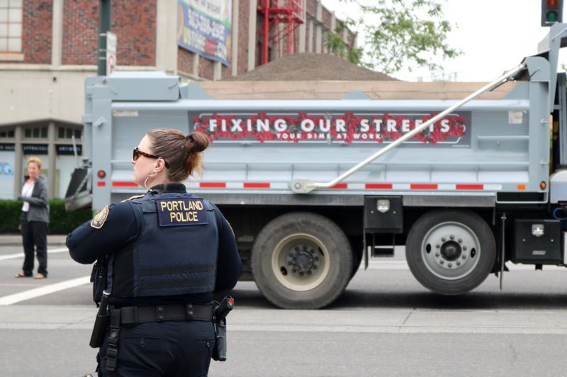 PMG PHOTO: ZANE SPARLING - A Portland Police Bureau surveys the scene near a Bureau of Transportation dump truck blocking an intersection near the Rose Quarter during the Grand Floral Parade on Saturday, June 8.
