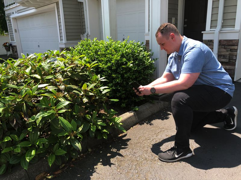 PMG PHOTO: STEPHANIE BASALYGA - Sean Lindemann, an Oregon account manager with ManageMowed, takes photographs at a Beaverton condominium development prior to putting together a work estimate.