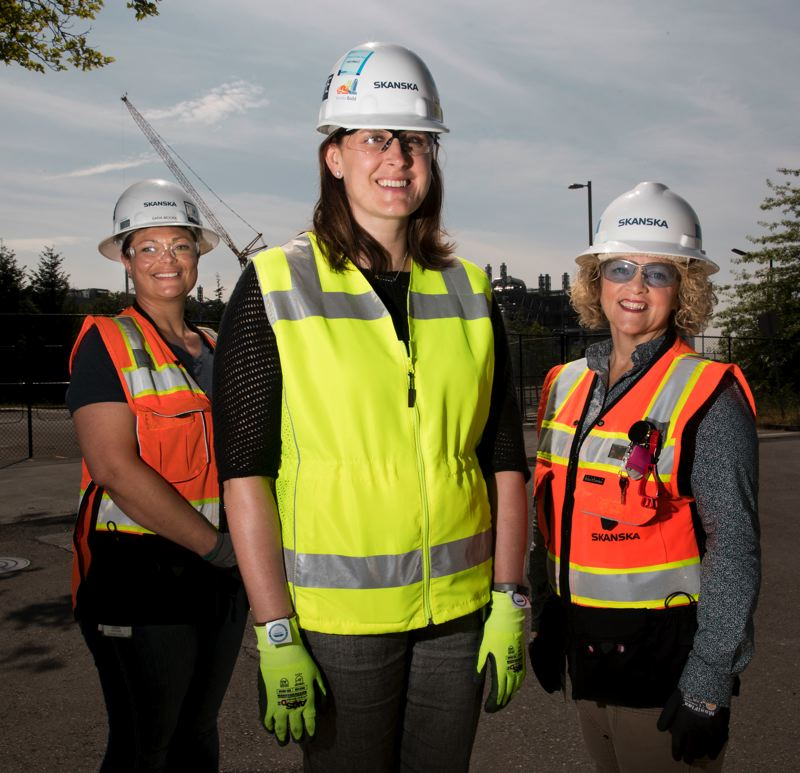 PMG PHOTO: JAIME VALDEZ - Sara Moore, left, and Rebecca Doc Kenney, right, recently moved from the trades into management-trainee positions as field engineers on a Skanska USA Building project in Hillsboro. The unique hiring approach was spearheaded by Katie Coulson, a vice president account manager with the general contractor.