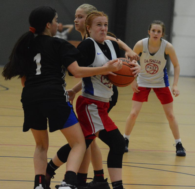PMG PHOTO: DAVID BALL - La Salles Ella Shackleton drives through a pair of defenders on her way to a layup in a first-round JV game Sunday.