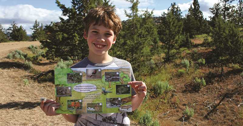 HOLLY SCHOLZ - Barnes Butte Elementary fifth grader Brendan Jones-Cunningham shows the Nature's Hide and Seek brochure and some rabbit fur that he found during the Kids in Parks scavenger hunt.