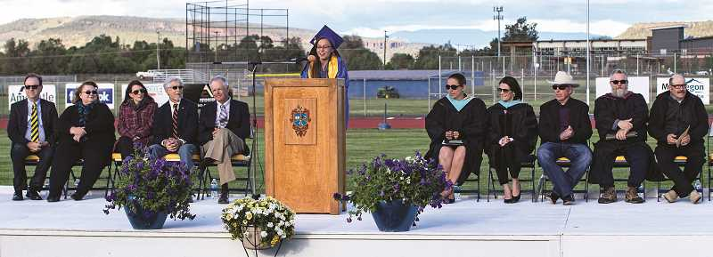 LON AUSTIN/CENTRAL OREGONIAN - CCHS valedictorian Olivia Cooper speaks during the ceremony. On the platform left to right: Crook County School District Board members Scott Cooper, Patti Norris, Gwen Carr, Walt Wagner and Doug Smith; CCHS Principal Michelle Jonas; CCSD Superintendent Dr. Sara Johnson; CCHS class of 1969 graduate Distinguished Alumnus Mike McCabe; CCHS English teacher and guest speaker Jim Churchill-Dicks; and Leeland Ashcraft, who accepted the Distinguished Alumnus award on behalf of his father, Daryle Ashcraft.