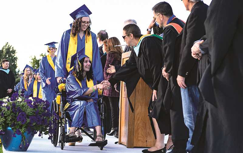 LON AUSTIN/CENTRAL OREGONIAN  - Bryanna Collins shakes hands with CCHS Principal Michelle Jonas as Rehgan Dill pushes her through the line.