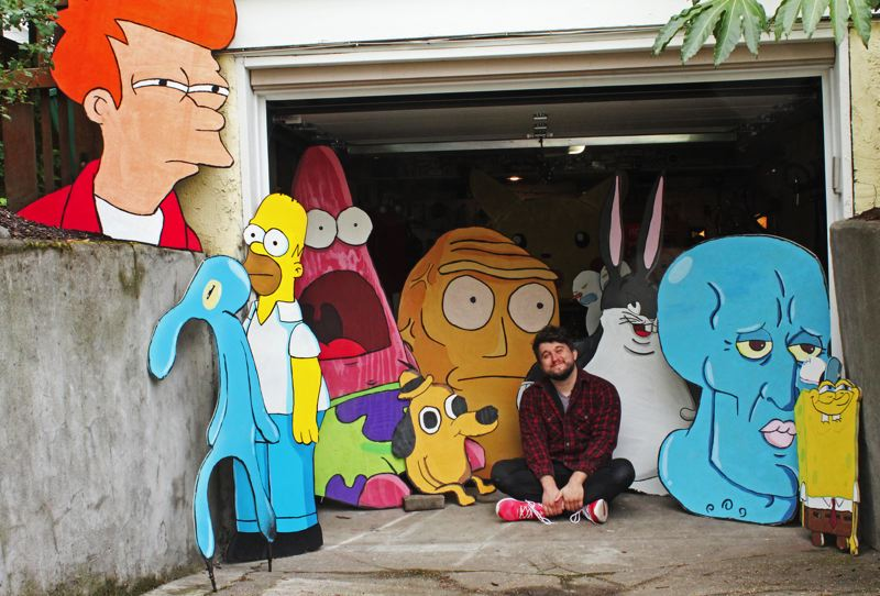 COURTESY: MIKE BENNETT - Mike Bennett sits in his garage with many of his collection of plywood cartoon characters that he has placed at various spots in Northeast Portland and elsewhere. Art drops are nothing new, 'but the scale (of work) is what makes them stand out,' he says.