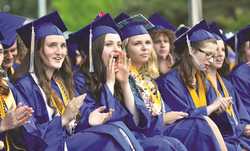 GRAPHIC PHOTO: GARY ALLEN - Grads applaud Hugh Anderson, who was chosen by students to be the commencement speaker at Friday's ceremony.