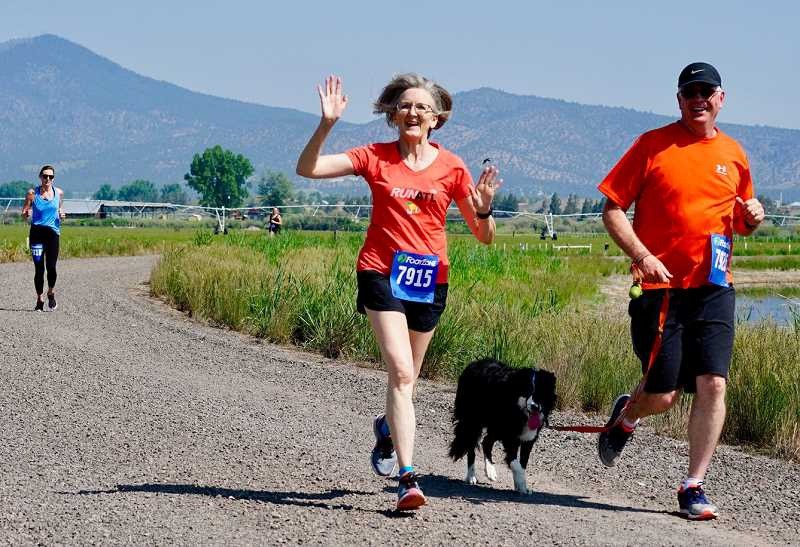 PHOTO COURTESY OF RACHEL WENDT CHANEY - Donna and Rod Barnes, along with their dog, skirt one of the lakes along the course during the Second Annual Wetlands Webfoot Waddle. The race is a fundraiser for the Crook County High School and Middle School cross country programs.