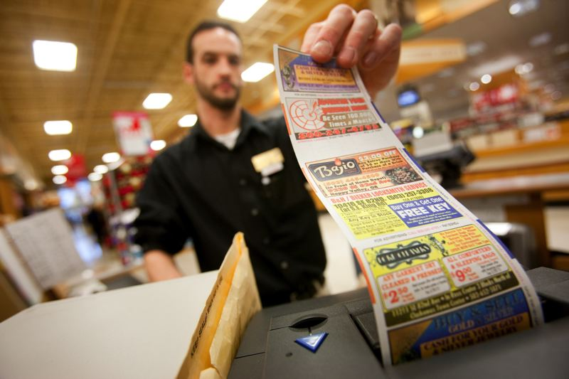 FILE PHOTO - A cashier grabs a receipt at the Johnson Creek Fred Meyer.