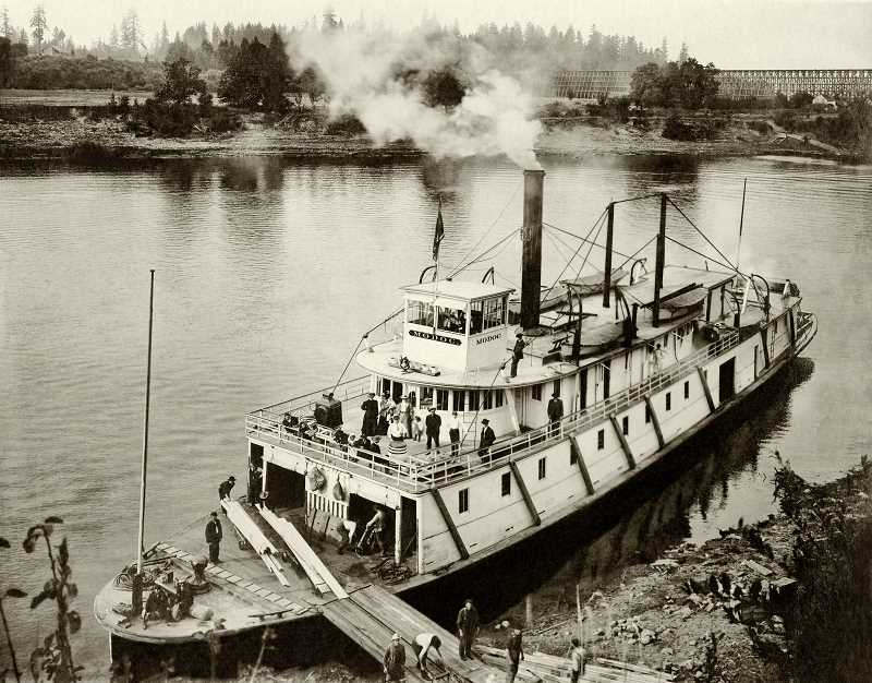 COURTESY PHOTO AND RESEARCH BY JOHN KLATT OF OLD OREGON PHOTOS; OLDOREGONPHOTOS.ORG - Sternwheeler Modoc at Wilsonville near new railroad trestle - 1907: This detailed photo shows the Oregon Railroad & Navigation river steamer Modoc taking on some lumber as it heads downstream on the Willamette River at Wilsonville.  In the background right is the newly completed railroad trestle, and also the south landing for Boones Ferry. The steamers dock area later was used as a gravel bunker, where gravel dredged from the river was stored before being loaded onto wagons to be carried to roads in the area.