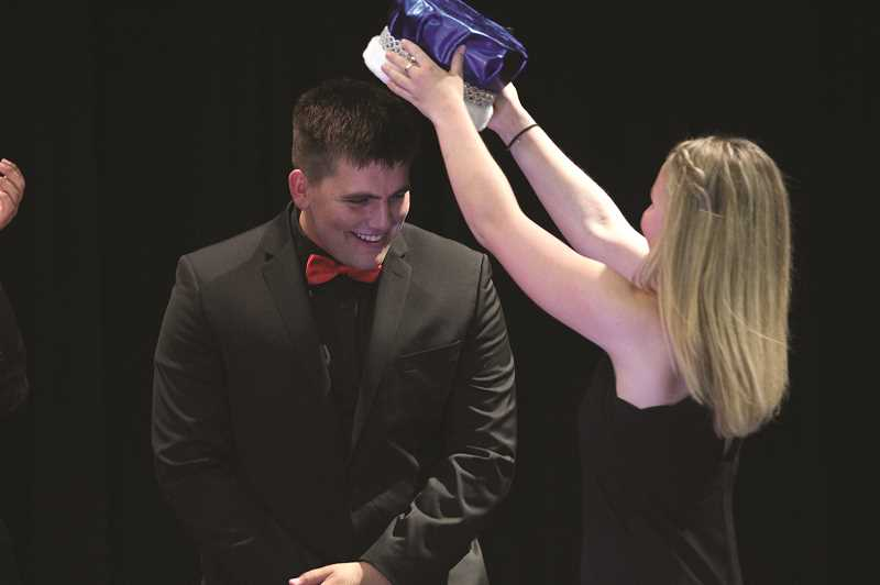 PMG PHOTO: PHIL HAWKINS - Nick Suing receives his crown from classmate Claire Seiler after winning the 2019 Mr. JFK Pageant.