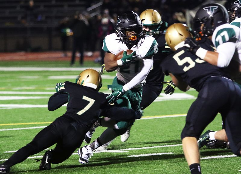 PMG PHOTO: DAN BROOD - Tigard High School graduating senior Malcolm Stockdale (with ball) will play at running back for the South squad in Saturday's Les Schwab Bowl.