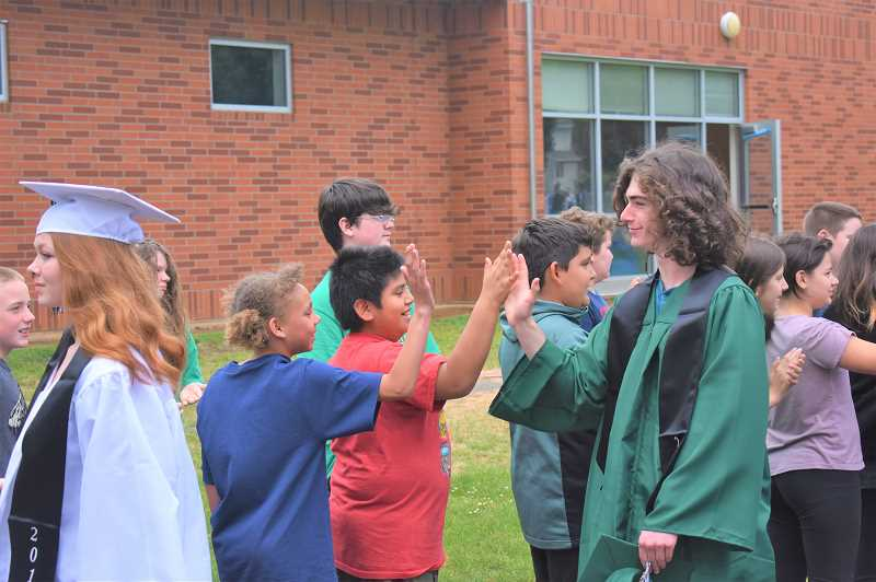 PMG PHOTO: EMILY LINDSTRAND - River Mill Elementary students high five Estacada High School seniors as the latter group takes their grad walk.
