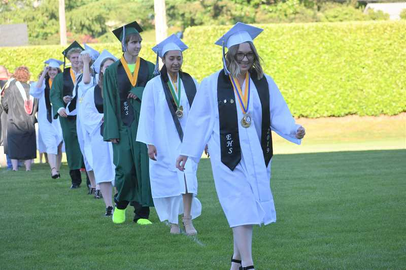 PMG PHOTO: EMILY LINDSTRAND - Soon-to-be Estacada High School graduates enter Buzz Randall Field as the 2019 commencement ceremony begins.