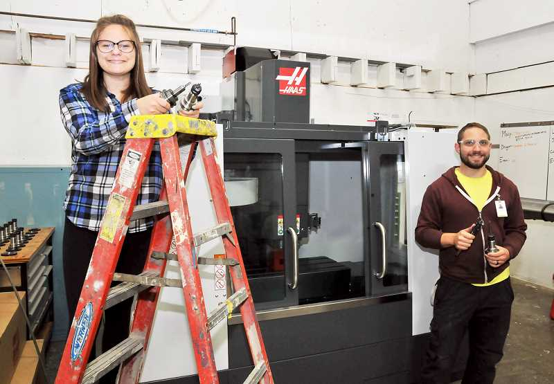 GRAPHIC PHOTO: GARY ALLEN - Tiger Manufacturing CEO Macy Showalter and shop trainer Jared Comfort pose with the brand new CNC lathe machine in the student-run company's shop at NHS. The machine cost $45,000.