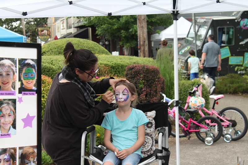 PMG PHOTO: HOLLY BARTHOLOMEW - A girl gets her face painted on opening night of the market.