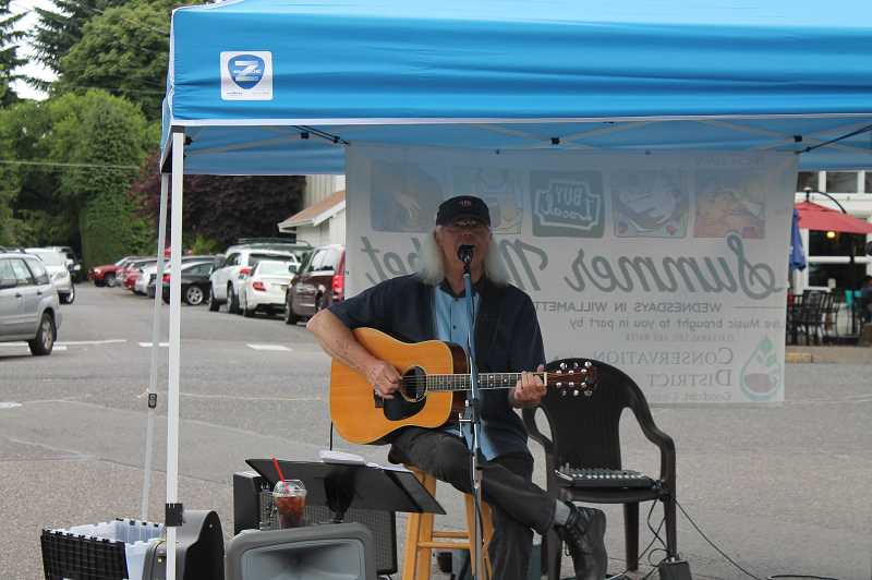 PMG PHOTO: HOLLY BARTHOLOMEW -  A man performs for the benefit of market patrons.