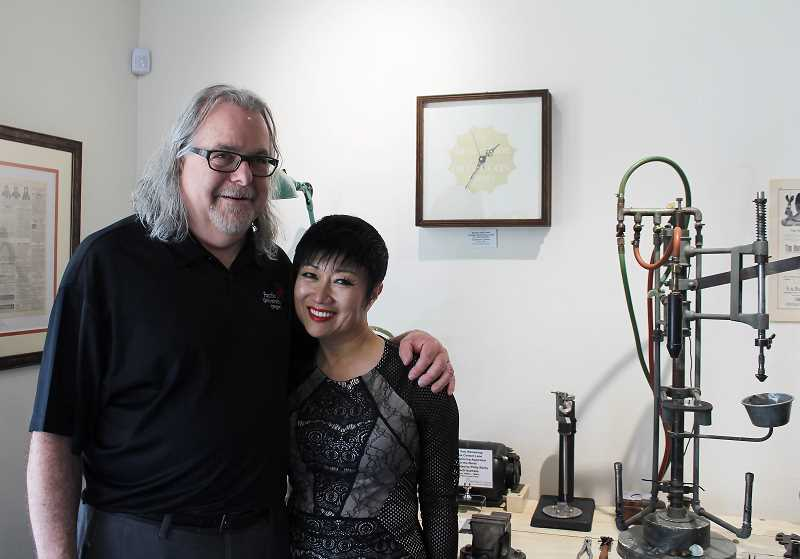 PMG PHOTO: SHELBY COKELEY  - Dr. Pat Caroline and his wife, Jiah Pack, stand in front of the still intact and functional glass contact lens machine, the only working apparatus they know of in the country.