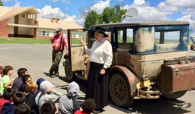 SUBMITTED PHOTO - Margee O'Brien gives historical perspective to third graders at Metolius Elementary, with the help of Dave Campbell, in front of his 1925 Chrysler. The students were engrossed, especially when learning what became of older catalogs.