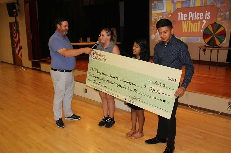 PMG PHOTO: JUSTIN MUCH - Graduating Woodburn High School seniors, left to right, Bailey Woolley, Kaylee-Abril Vasquez Reyes and Jose Carlos Ochoa Delgado ceremoniously receive a check for the Tulip Tee-Up Scholarship at Woodburn Estates & Golf on Thursday, June 13.