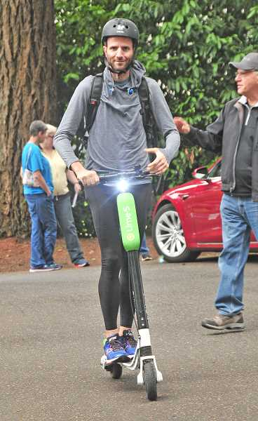 REVIEW PHOTO: VERN UYETAKE - Lake Oswego City Councilor Joe Buck goes for a spin on an electric scooter Sunday at the EV Fair.